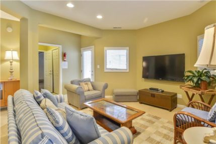 The lower level off the garage has a large seating area and a large screen tv.