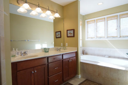 The bathroom in the second master bedroom has a jacuzzi, walk-in shower, and two sinks.
