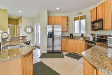 The kitchen has modern appliances, granite countertops, and is fully stocked.