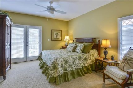 The master bedroom is tastefully decorated with a tropical theme and has a king size bed.